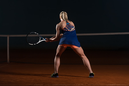 Female Tennis Player Reaching To Hit The Tennis Ball On Court - Back View