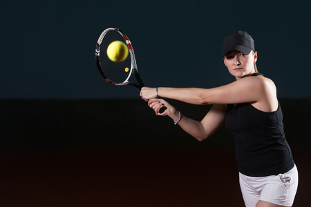 Female Tennis Player Reaching To Hit The Tennis Ball On Court