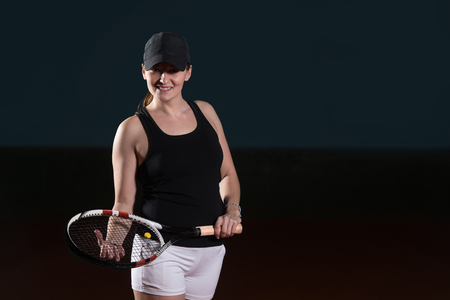 Portrait Of Female Tennis Player With Racket Ready To Hit A Tennis Ball