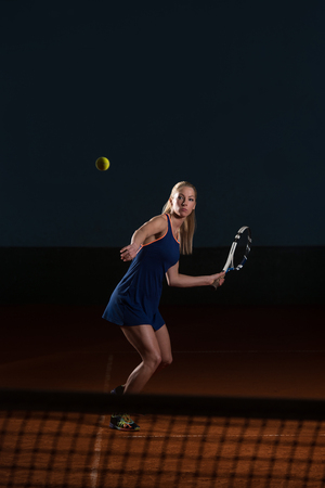 Young Female Tennis Player With Racket Ready To Hit A Tennis Ball