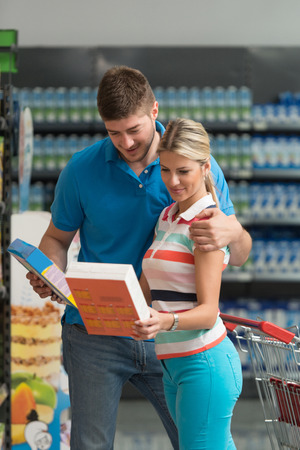 Beautiful Young Couple Shopping For Flakes For Breakfast In Produce Department Of A Grocery Store - Supermarket - Shallow Deep Of Field