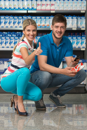 Beautiful Young Couple Showing Thumbs Up Sign In Supermarket Shopping For Milk And Cheese In Produce Department Of A Grocery Store - Shallow Deep Of Field