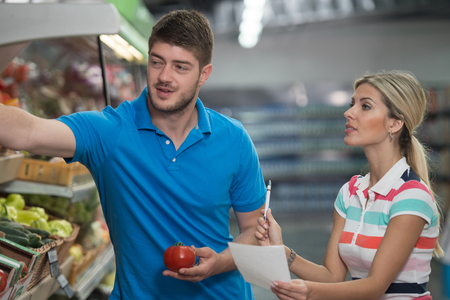 Beautiful Young Couple Looking At The Grocery List Shopping For Fruits And Vegetables In Produce Department Of A Grocery Store - Supermarket - Shallow Deep Of Field