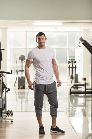 Portrait of a Young Physically Fit Man in White T-shirt Showing His Well Trained Body - Muscular Athletic Bodybuilder Fitness Model Posing After Exercises