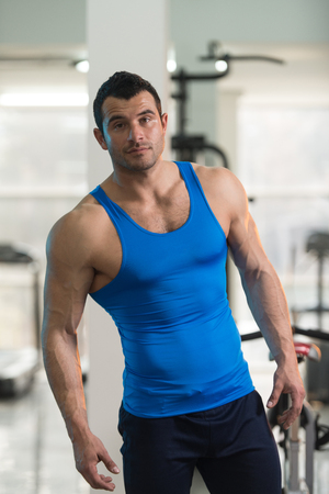 Portrait Of A Young Physically Fit Man In Blue Undershirt Showing His Well Trained Body - Muscular Athletic Bodybuilder Fitness Model Posing After Exercises