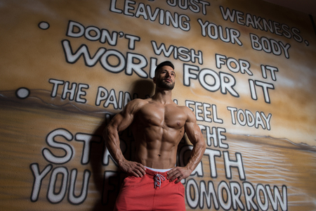 Portrait of a Young Physically Fit Man in White T-shirt Showing His Well Trained Body - Muscular Athletic Bodybuilder Fitness Model Posing After Exercises In Front Of A Graffiti Wall