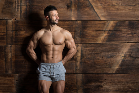 Portrait of a Young Physically Fit Man Showing His Well Trained Body While Wearing Sports Shorts - Muscular Athletic Bodybuilder Fitness Model Posing After Exercises on Wooden Wall - a Place for Your Text