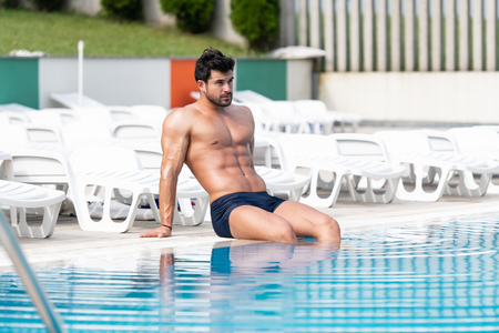 Fashion Portrait Of A Very Muscular Sexy Man In Swimsuit At Swimming Pool