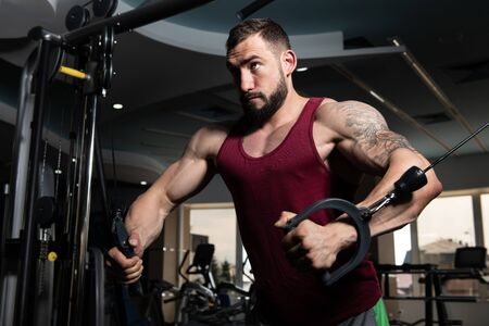 Photo for Handsome Muscular Fitness Bodybuilder Doing Heavy Weight Exercise For Chest On Machine With Cable In The Gym - Royalty Free Image