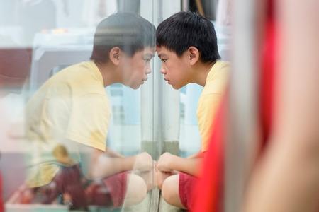 Photo pour Sad upset waiting boring depressed child (boy) near a window, reflection. - image libre de droit