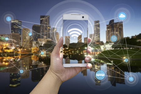 Photo pour Hand holding white phone with city scape and wifi network connection concept - image libre de droit