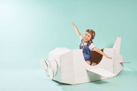 Photo for Little cute girl playing with a cardboard airplane. White retro style cardboard airplane on mint green background . Childhood dream imagination concept . - Royalty Free Image
