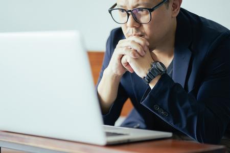 Photo pour Close Up view of serious businessman looking on screen of laptop . - image libre de droit