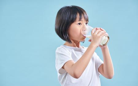 Photo pour Cute smart asian little girl drinking milk on blue background - image libre de droit