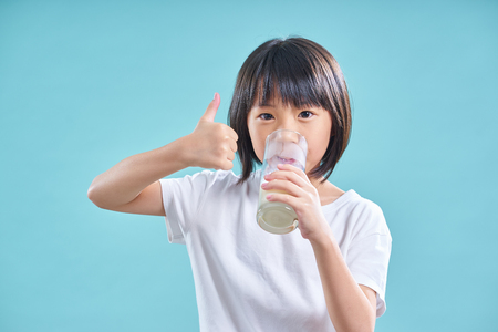 Foto de Asian little girl enjoy to drinking glass of milk isolated on light blue background  . - Imagen libre de derechos