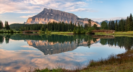 Rundle mountain reflected in pond with two bridges
