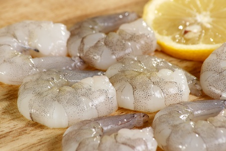 raw king prawns on a wooden board with a slice of lemon