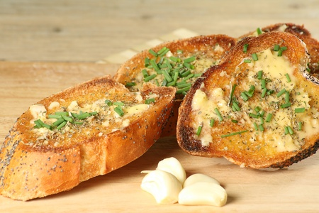 slices of toasted garlic bread with chopped chives on a wooden board