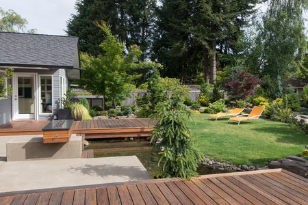 Back yard of a modern Pacific Northwest home featuring a deck spanning a creek-like water feature with a landscaped lawn and two inviting lawn chairs in the background.