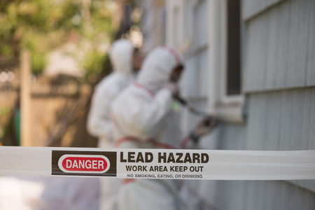 Foto de Two house painters in hazmat suits removing lead paint from an old house. - Imagen libre de derechos