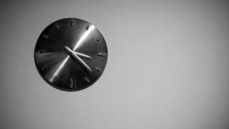 Metal wall clock hanging on the white wall