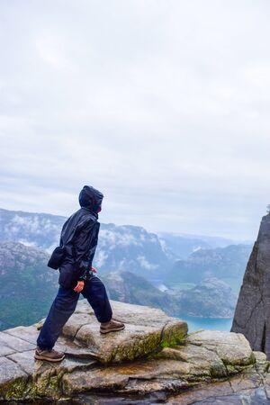 Photo pour Girl on Prekestolen or Pulpit Rock in the rain. Norway. - image libre de droit