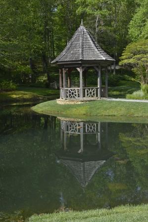gazbo and grass by a pond