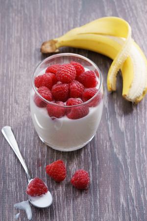 raspberries, banana and yogurt. fresh berries on white fabric