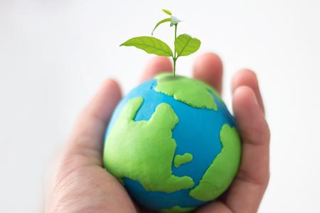 Photo pour Globe on hand with plant, safe the world , CSR Abbreviation or Corporate Social Responsibility concept - image libre de droit