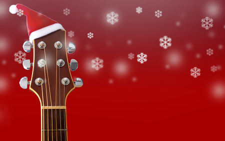 Foto de Red Christmas hat on guitar with snow and red background, Merry Christmas song - Imagen libre de derechos