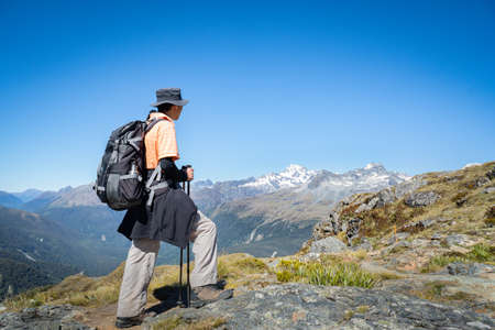 Photo for A backpacker enjoying panorama views of the mountain ranges on day 2 of the Routeburn Track, South Island. - Royalty Free Image