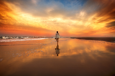 Photo pour woman walking on the beach near the ocean at the sunset - image libre de droit