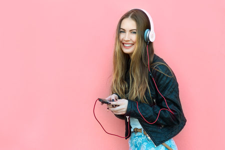 beautiful happy woman in headphones listening music near the wall