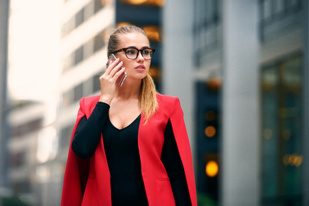 Elegant businesswoman walk in city financial district and talking on cell phone wearing jacket and eyeglasses. Succesful business woman walking near skyscrapers.