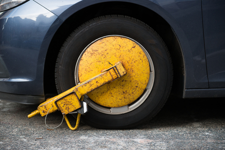 Photo pour Car wheel blocked by wheel lock because illegal parking violation - image libre de droit