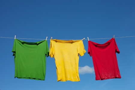 T-shirts on clothesline against blue sky