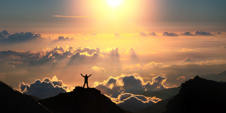 Photo pour A man standing on the top of the mountain above the clouds. - image libre de droit