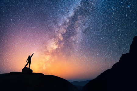 Catch the star. A person is standing next to the Milky Way galaxy pointing on a bright star.