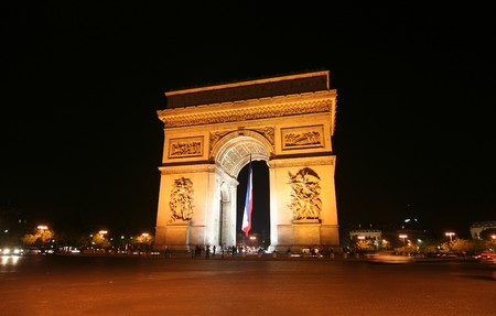 Arc de Triomphe with French flag at night