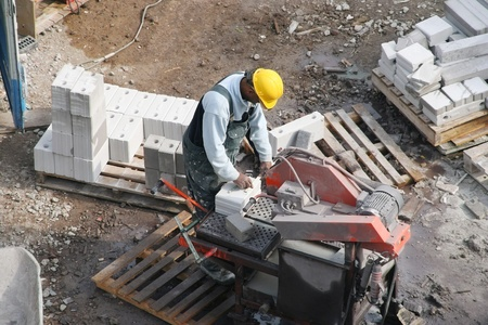Photo for Black construction worker operating a brick-cutting machine at a construction site. Picture taken on April 13, 2007 in The Hague, Holland - Royalty Free Image