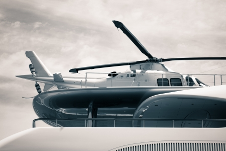 Detail of luxury yacht with helicopter on the deck, digitally retouched and toned photo.