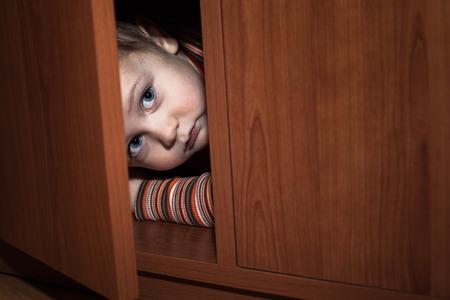 Scared child boy hiding in wardrobe