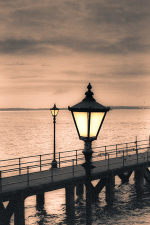 Moody sky and vintage streetlamp on the coast. Toned grainy 35mm film scan.