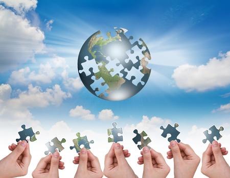 Photo pour Business concept with a hand building puzzle globe - image libre de droit