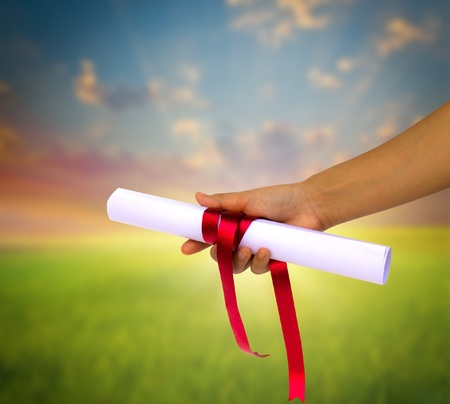 Photo pour Hand holding Diploma wrapped with a red ribbon. - image libre de droit