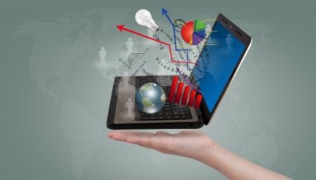 Foto de Hand show Laptop and financial Graphs - Imagen libre de derechos