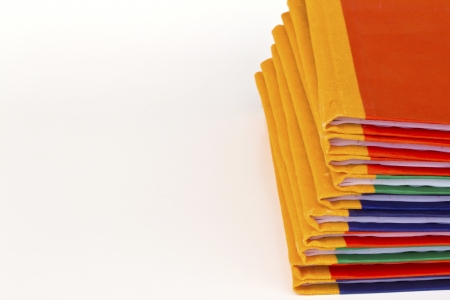 Stack of colorful books on white background, partial view.