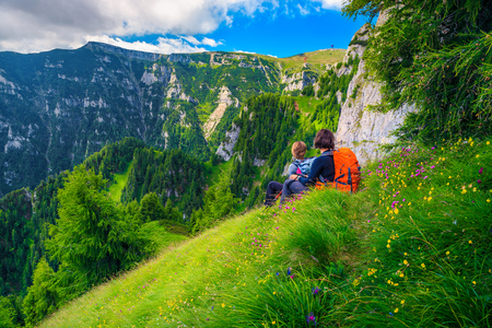 Photo for Sporty woman's hiking team with colorful backpacks relaxing and enjoying the view on narrow trekking trail, Bucegi mountains, Carpathians, Transylvania, Romania, Europe - Royalty Free Image