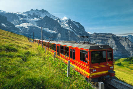 Photo pour Mountain railroad with modern cogwheel red tourist train on the slope. One of the most famous railway, Jungfraujoch, Kleine Scheidegg, Grindelwald, Bernese Oberland, Switzerland, Europe - image libre de droit