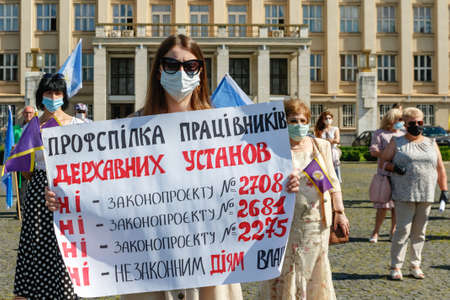 Uzhgorod, western Ukraine - June 30, 2020: A union worker in a protective mask holds a banner during a protest against anti-professional bill No. 2681 during quarantine.